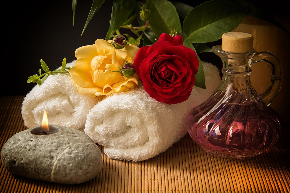 The Best Bamboo Towels with flowers, a stone, and massage oil on a bamboo mat