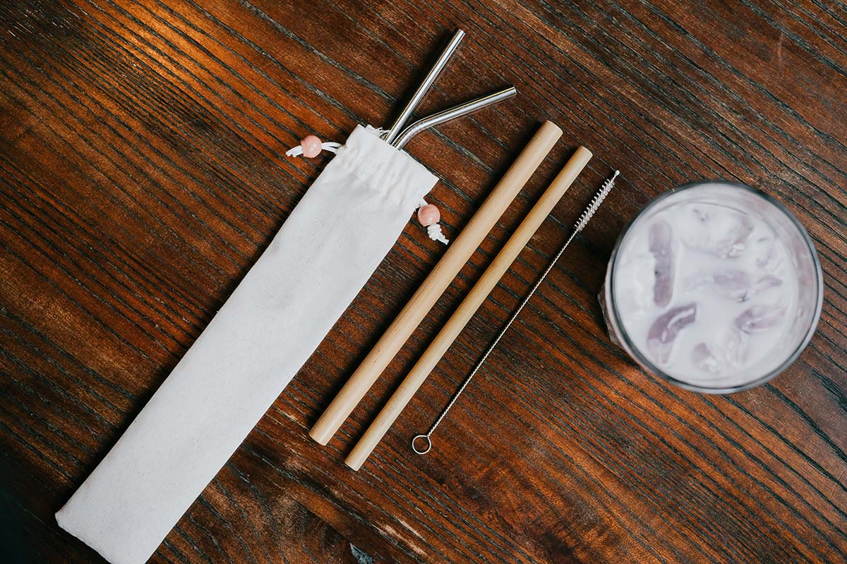 Bamboo straws set and steel straws set on a table next to a glass with a beverage