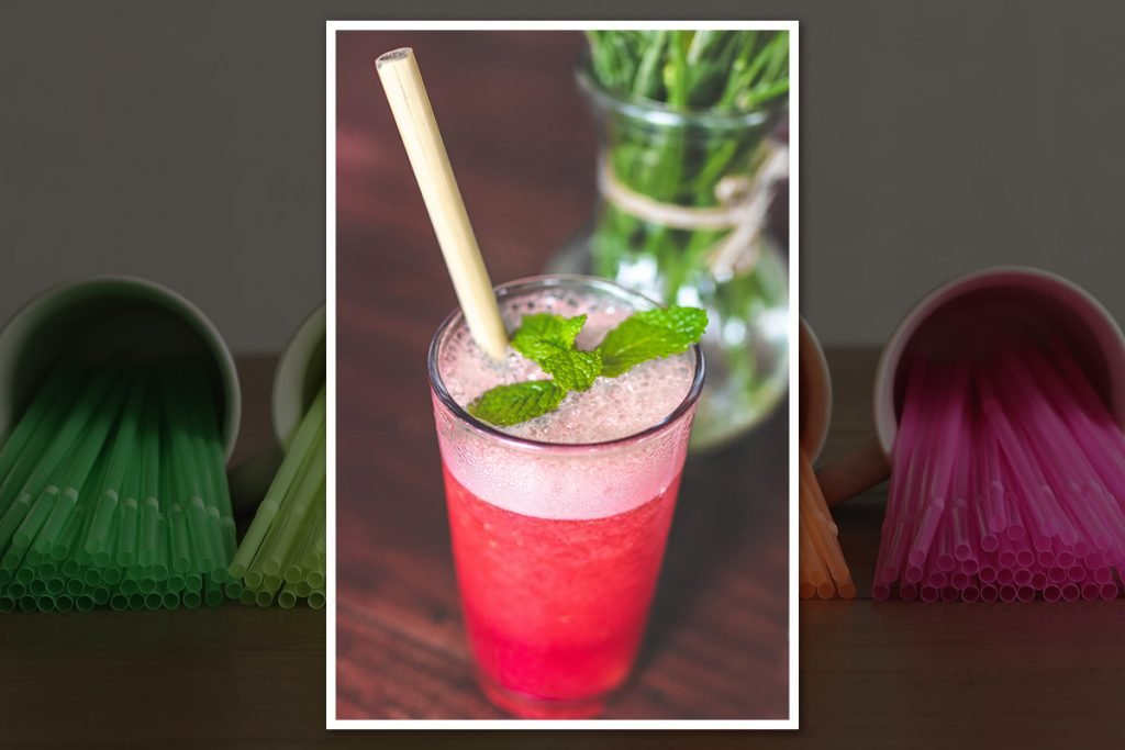 Drink with bamboo straw in the center and the background there are plenty of plastic straws with a dark overlay