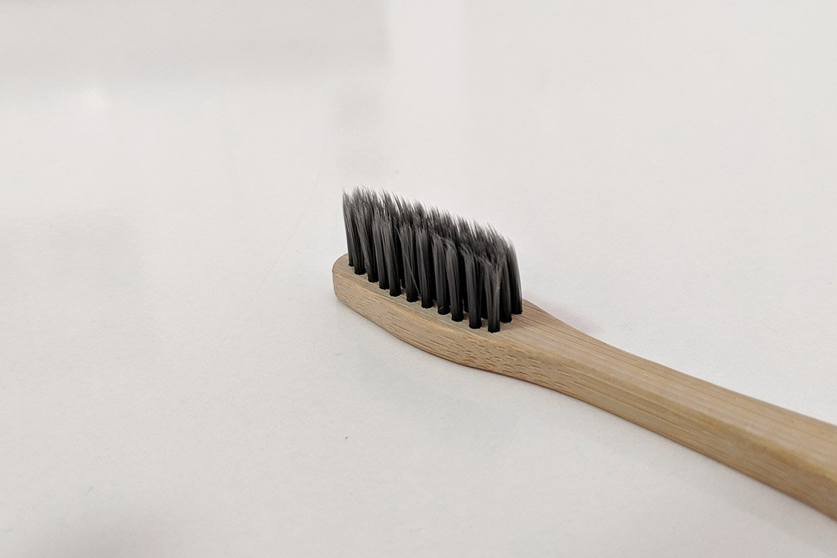 Bamboo toothbrush with dark bristles on a white table