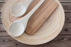 Bamboo kitchen utensils on a bamboo cutting board and a bamboo plate, which is on a wooden table