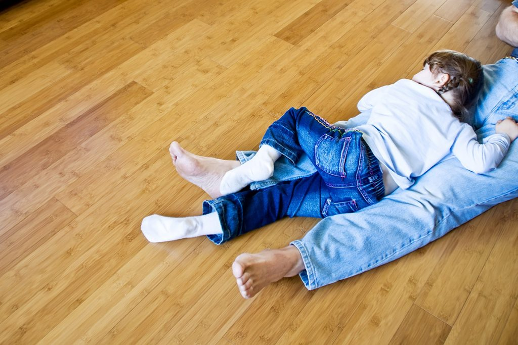 Little girl and another person laying on bamboo flooring
