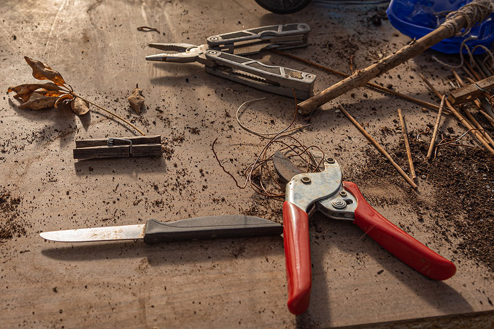 Pruning shears, knife, and pliers on a table with soil and bamboo sticks