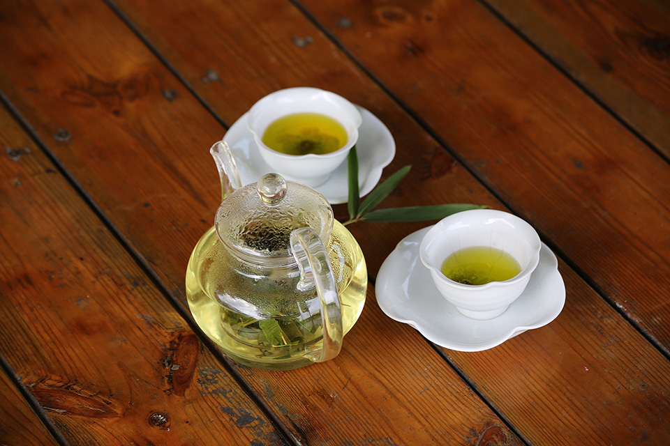 Two cups of bamboo tea and a glass can with bamboo leaf tea on a wooden table with a bamboo leaf