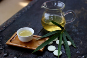 Cup of bamboo tea and glass tea can with bamboo tea on a table with bamboo leaf, pebbles, and little tray as decoration