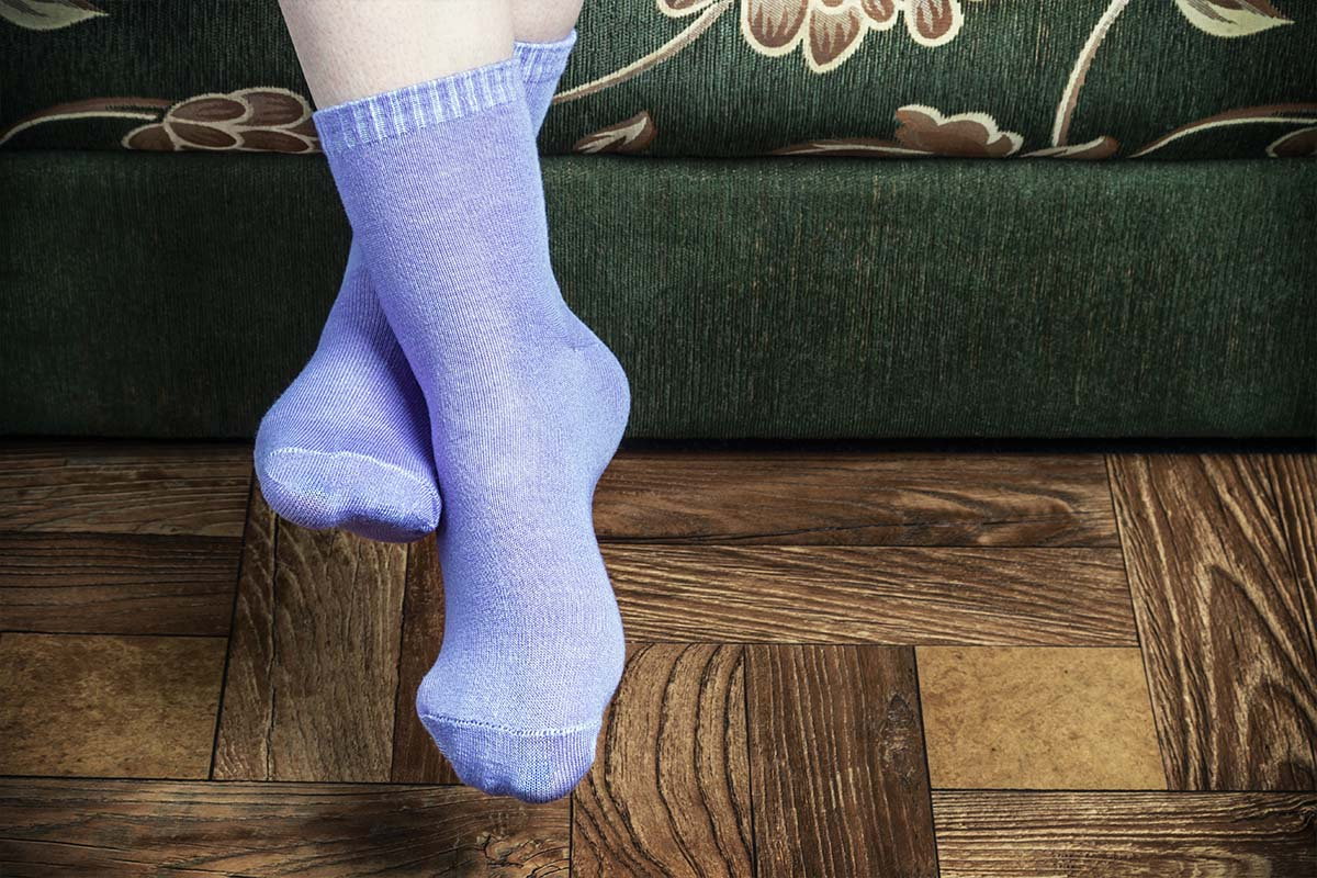 Legs of a person sitting on a green couch wearing purple colored bamboo socks