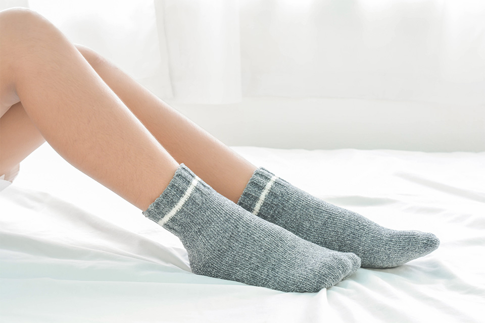 Person wearing grey bamboo socks on a bed