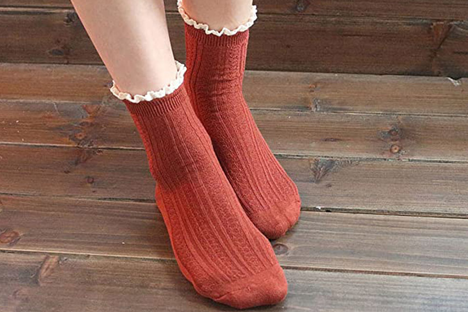 Feet of a person wearing red bamboo socks on a wooden floor
