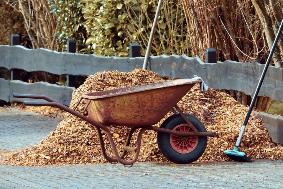 Empty wheelbarrow next to a pile of mulch, a fence and a broom