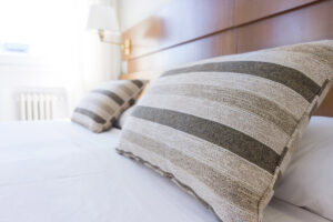 Two multi colored bamboo pillows on a bed