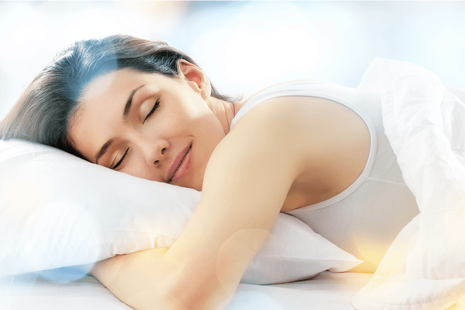 Young women smiles in sleep while her hands under the pillow