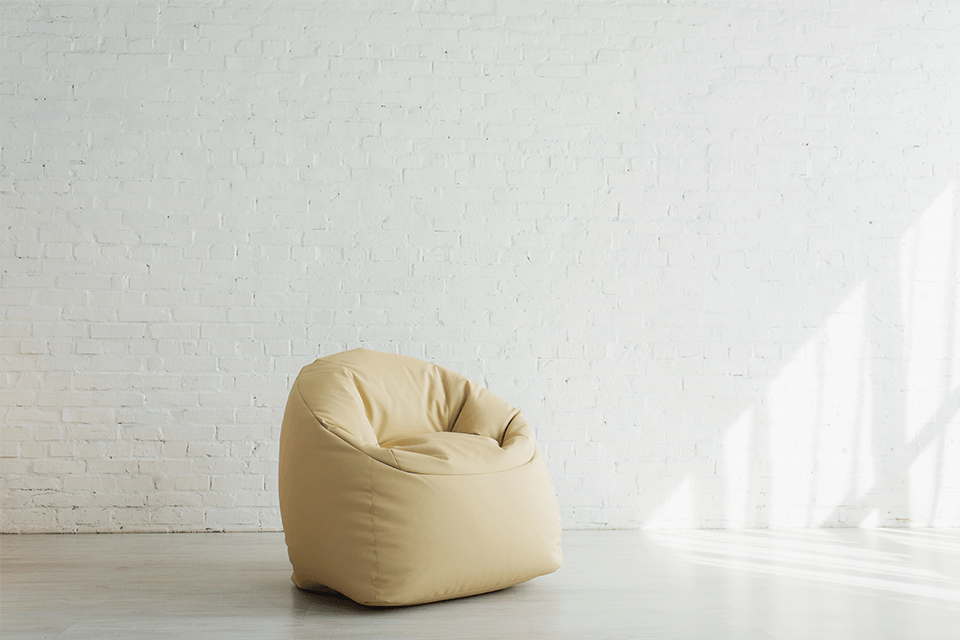 Sunlight near beige bean bag chair near brick wall in modern home