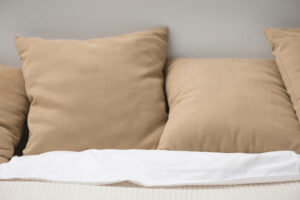Close up of brown pillows on cozy empty bed with text