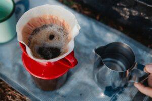 Crop hiker preparing coffee in carafe on fabric